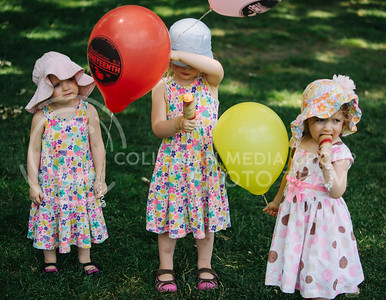 Cara,2, Elanor, 3, and Grace Mann, 2, hold their balloons during the Juneteenth celebration in City Park on June 6, 2017. (Emily Starkey | The Collegian)