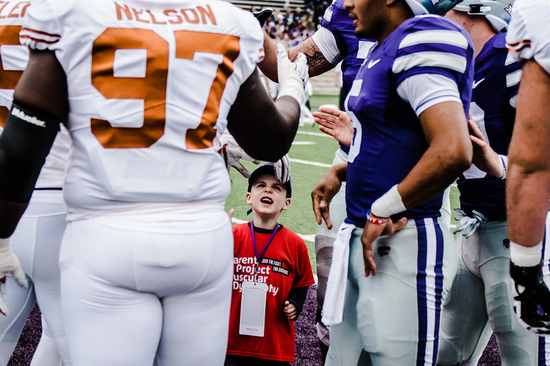 Team captains shake hands while the honory captain of the game watches before the game against Texas in Bill Snyder Family Stadium on Sept. 29, 2018. The Wildcats fell to the Longhorns 19-14. (Meg Shearer | Collegian Media Group)