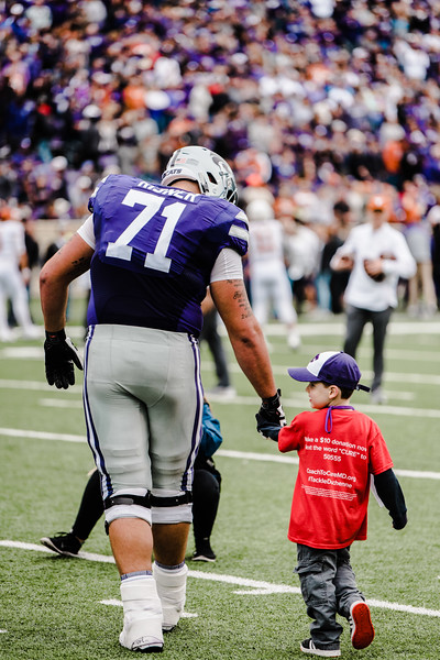 Head-captain Dalton Risner walks onto the field with his honory captain of the game to do the coin toss before the game against Texas in Bill Snyder Family Stadium on Sept. 29, 2018. The Wildcats fell to the Longhorns 19-14. (Meg Shearer | Collegian Media Group)
