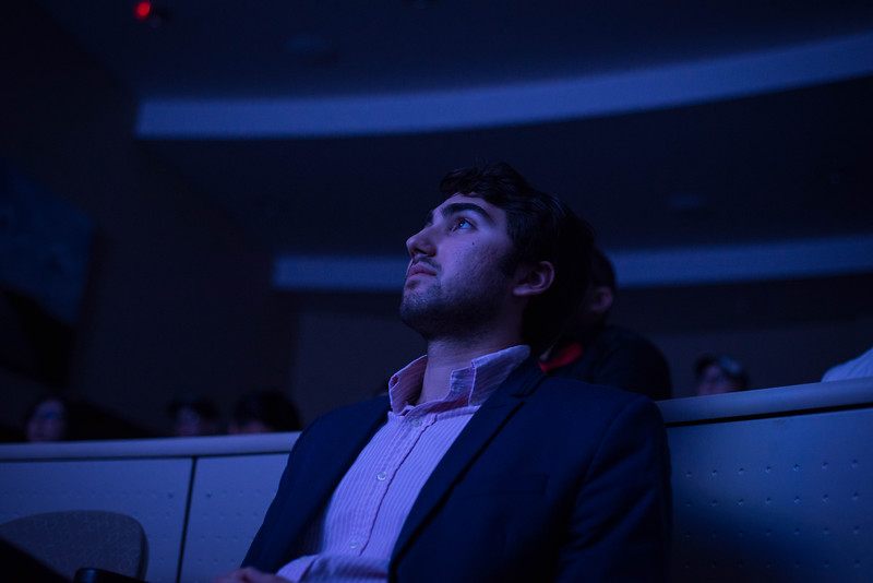 """UPC Member Alex Wacom watches the first film during the K-State 48 flim festival. Wacom later presented the second place award for the film """"Dear Deborah""""."""