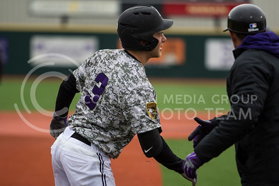 Freshman center fielder, Cameron Thompson, high fives his coach after hitting a triple during the K-State game against UC Riverside at Tointon Stadium on Mar. 12 2017. (Sabrina Cline | The Collegian)