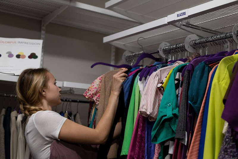 Laura Wiebe, senior in apparel and textiles, helps organize the donated clothes in the Career Closet. During the week of the career fair, an average of 100 students visit the Career Closet. (Alex Todd | Collegian Media Group)