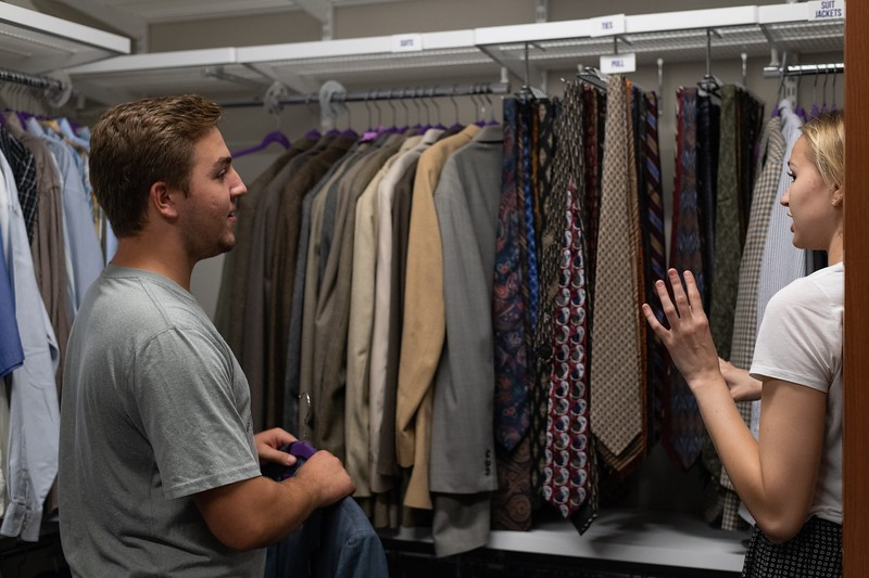 Sophomore Carson Avery gets some fashion tips from Laura Wiebe, a senior in apparel and textiles. During the week of the career fair, the Career Closet has about 100 student visitors every day. (Alex Todd | Collegian Media Group)