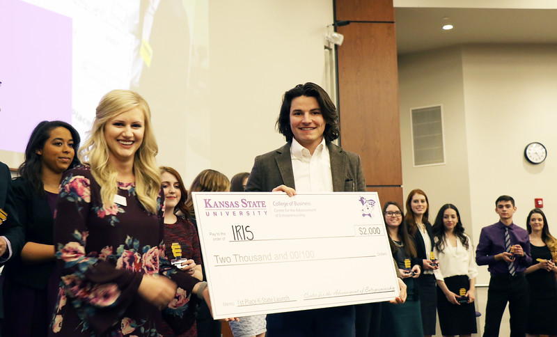 Chris Zachary, senior in entrepreneurship, receives the grand prize of $2,000 at K-State Launch on Wednesday, March 14, 2018, in the College of Business Building. Zachary was selected for his venture idea of IRIS, which he described as a web platform for marketing video for professional services. Also shown: Morgan Dreiling, senior in entrepreneurship and program associate for the Center for the Advancement of Entrepreneurship. (Tiffany Roney | Collegian Media Group)