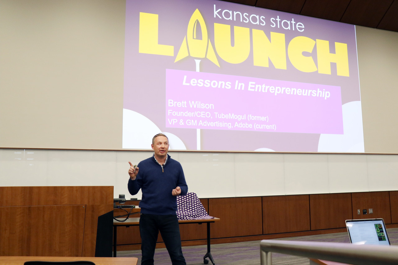 Brett Wilson, who founded TubeMogul, which Adobe acquired for $540 million, speaks at K-State Launch on Wednesday, March 14, 2018, in the College of Business Building. K-State Launch is an entrepreneurial idea competition for K-State students who have new venture ideas.  <br /> <br /> Wilson, who has been featured in the Wall Street Journal and the New York Times, provided five tips for prospective entrepreneurs: 1) Make your college your lab. Wilson advised students to use the resources currently available to them while they are in school, including the possibility of calling alumni entrepreneurs to seek feedback on their ideas. 2) Be aware that culture is everything. Wilson said a great company culture attracts likeminded people. 3) Ride the tsunami. Wilson advised students to try to jump into big venture markets where growth is already happening. 4) Destroy the status quo. His company gained a platform by calling out issues in how major competitors treated customers and handled business. The TubeMogul brand was strengthened as its leaders told the truth about problems in their sphere, Wilson said. 5) Stay self-aware. Wilson knew when to sell and is now vice president and general manager of advertising at Adobe. (Tiffany Roney | Collegian Media Group)