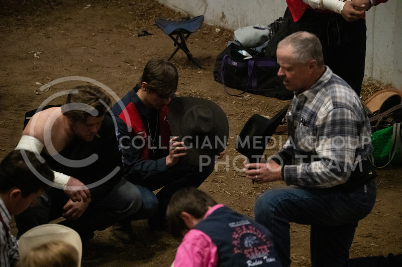 all the riders gather around for a group prayer before the rode starts at Weber Arena at the 2020 Kansas State rodeo. (Dalton Wainscott | Collegian Media Group)
