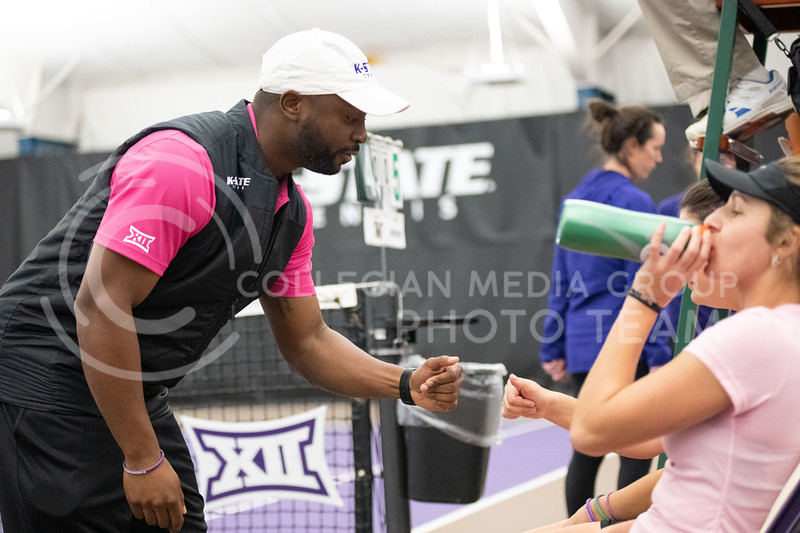 K-State's coach, Jordan Smith, talks with Anna Turco and Margot Decker as they face off against Washington at Body First Tennis Center in Manhattan, KS. 02/14/20. (Dylan Connell | Collegian Media Group)