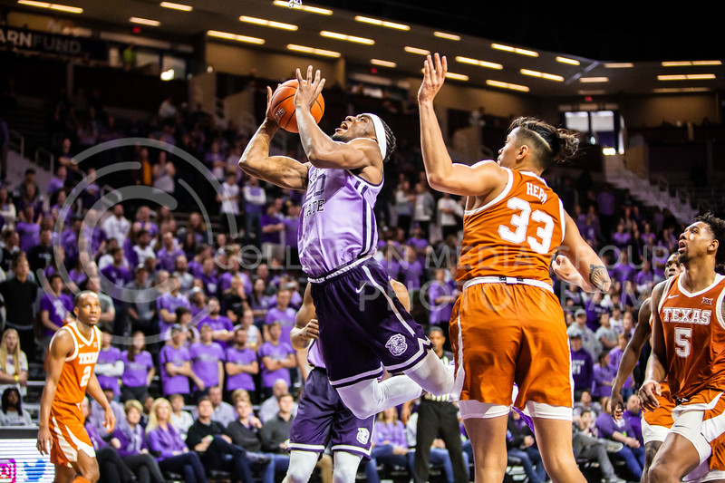 Senior forward Xavier Sneed is fouled as he charges the basket during K-State's men's basketball Throwback Game against Texas in Bramlage Coliseum on Feb. 22, 2020. For the Throwback Game, K-State wore two-tone lavender uniforms, which were worn from 1973 to 1982. The Longhorns took the Wildcats 70-59. (Logan Wassall | Collegian Media Group)