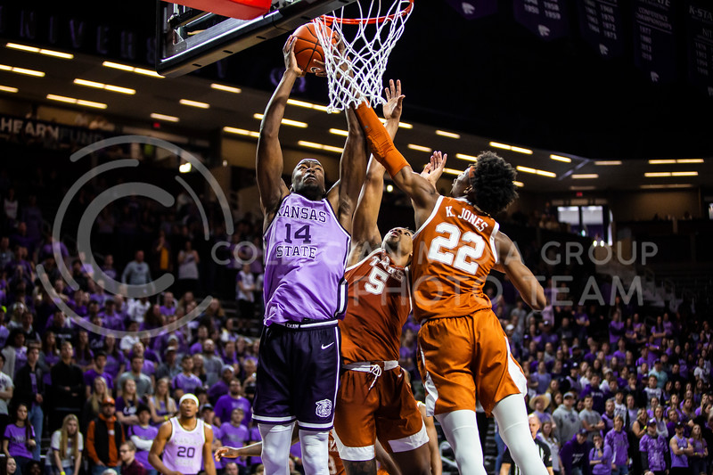 Senior forward Makol Mawein leaps up towards the basket for a dunk during K-State's men's basketball Throwback Game against Texas in Bramlage Coliseum on Feb. 22, 2020. For the Throwback Game, K-State wore two-tone lavender uniforms, which were worn from 1973 to 1982. The Longhorns took the Wildcats 70-59. (Logan Wassall | Collegian Media Group)
