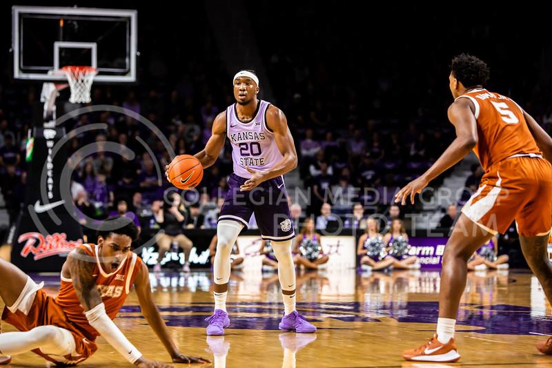 Senior forward Xavier Sneed scans the court for an open play during K-State's men's basketball Throwback Game against Texas in Bramlage Coliseum on Feb. 22, 2020. For the Throwback Game, K-State wore two-tone lavender uniforms, which were worn from 1973 to 1982. The Longhorns took the Wildcats 70-59. (Logan Wassall | Collegian Media Group)