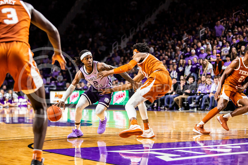 Junior guard Cartier Diarra looks across the court for an open play during K-State's men's basketball Throwback Game against Texas in Bramlage Coliseum on Feb. 22, 2020. For the Throwback Game, K-State wore two-tone lavender uniforms, which were worn from 1973 to 1982. The Longhorns took the Wildcats 70-59. (Logan Wassall | Collegian Media Group)