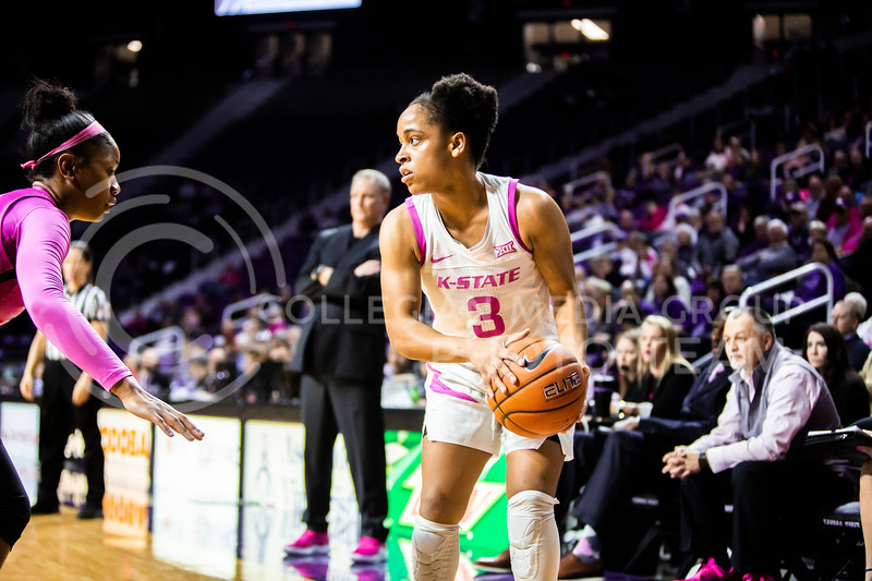 Senior guard Angela Harris looks across the court for an open play during K-State's women's basketball team's Play 4 Kay Pink Game to promote cancer awareness. K-State played against TCU in Bramlage Coliseum on Feb. 19, 2020. The Horned Frogs defeated the Wildcats 54-52. (Logan Wassall | Collegian Media Group)