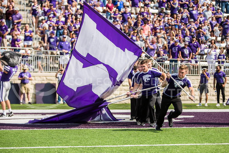 K-State yell leaders rush out onto the field with K-S-T-A-T-E flags before the football game against Bowling Green in Bill Snyder Family Stadium on Sept. 7, 2019. The Wildcats shut down the Falcons with a final score of 52-0. (Logan Wassall | Logan Wassall Collegian Media Group)