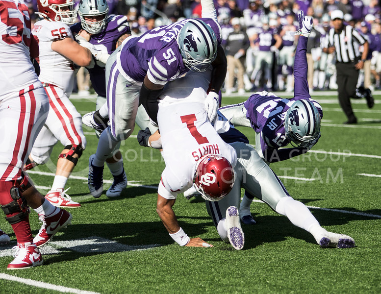 Senior defensive end Reggie Walker and sophomore defensive end Wyatt Hubert tackle Oklahoma's quarterback Jalen Hurts during the game against Oklahoma at Bill Snyder Family Stadium on Oct. 25, 2019. (Sabrina Cline | Collegian Media Group)