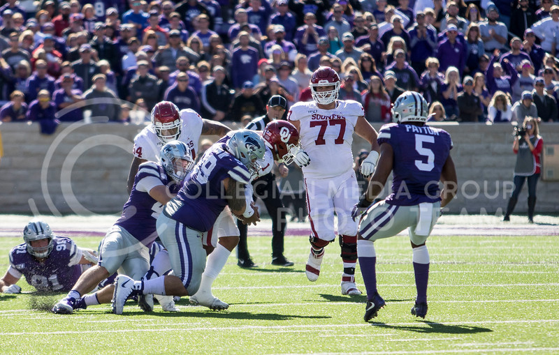 Senior defensive tackle Trey Dishon and teammates take down Oklahoma's quarterback Jalen Hurts during the game against Oklahoma at Bill Snyder Family Stadium on Oct. 26, 2019. (Sabrina Cline | Collegian Media Group)