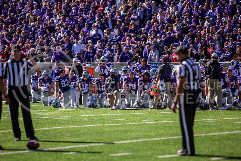 K-State's football team kneels as they wait for their injured teammate (senior linebacker Eric Gallon II) to be taken off the field during K-State's homecoming football game against OU in Bill Snyder Family Stadium on Oct. 26, 2019. The Wildcats upset the No. 5 rated Sooners with a final score of 48-41. (Logan Wassall | Collegian Media Group)