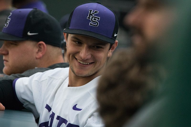 Junior Brett Lockwood smiles at teamate in KSU dugout at game against TCU, the Wildcats won 7-4 at Tointon Stadium in Manhattan. The baseball team held a fundraiser along with the game, in coordination with the Silver Key Sophomore Honorary.  (Dalton Wainscott I Collegian Media Group)