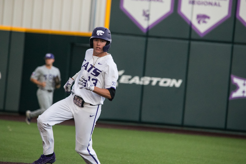 Junior Caleb Littlejim looks to third base coach to see if he should run to third at game against TCU, the Wildcats won 7-4 at Tointon Stadium in Manhattan. The baseball team held a fundraiser along with the game, in coordination with the Silver Key Sophomore Honorary. (Dalton Wainscott I Collegian Media Group)