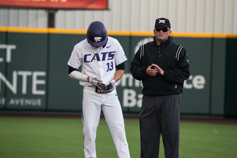 Junior Caleb Littlejim adjusts gloves on second base at game against TCU, the Wildcats won 7-4 at Tointon Stadium in Manhattan. The baseball team held a fundraiser along with the game, in coordination with the Silver Key Sophomore Honorary. (Dalton Wainscott I Collegian Media Group)