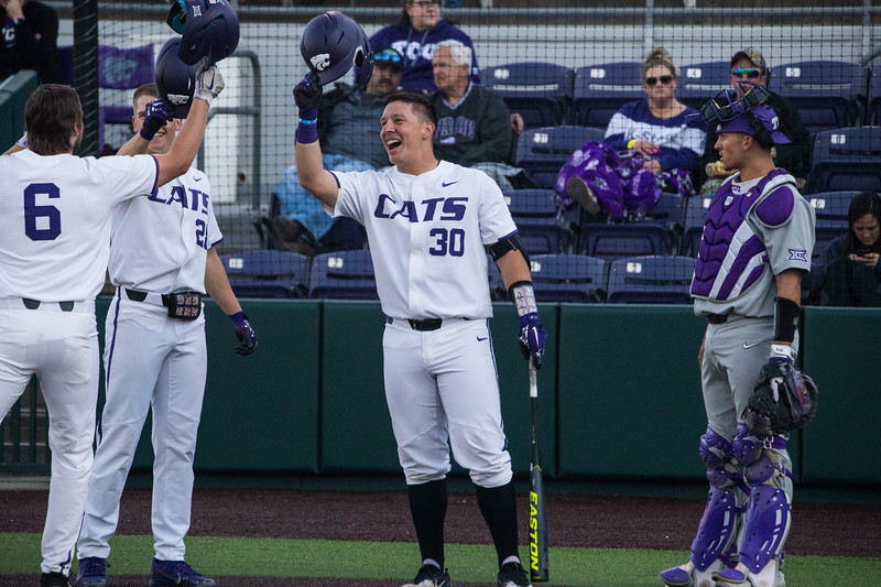 Terrence Spurlin, Zach Kokoska and Chris Ceballos knock helmets after 2 run drive at game against TCU, the Wildcats won 7-4 at Tointon Stadium in Manhattan. The baseball team held a fundraiser along with the game, in coordination with the Silver Key Sophomore Honorary. (Dalton Wainscott I Collegian Media Group)