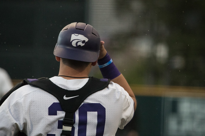 Catcher Junior Chris Ceballos adjusts helmet at game against TCU, the Wildcats won 7-4 at Tointon Stadium in Manhattan. The baseball team held a fundraiser along with the game, in coordination with the Silver Key Sophomore Honorary. (Dalton Wainscott I Collegian Media Group)