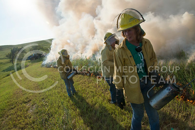 Debbie Sunerour, research technician for biology at K-State, moves her head away from the flames as Greg Zolnerowich, professor of entomology, finishes the burn line of a 'watershed' on the Konza Prairie on July 26, 2016. (Evert Nelson | The Collegian)