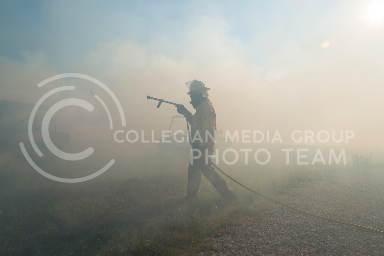 Greg Zolnerowich, professor in entomology, emerges with a waterhose from the smoke on a burn of a watershed on the Konza Prairie on July 26, 2016. The Konza Prairie Biological Station performed the burn as research into different burning times and the effect it has on the ecosystem of the Konza Prairie. (Evert Nelson | The Collegian)