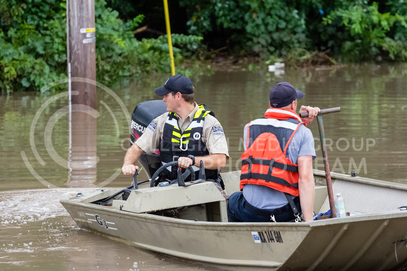 Two emergency responders work to launch an additional boat to aid recovery efforts. Manhattan Fire Department, Riley County Police Department and Pottawatomie County Sheriff's department work together to help recover Manhattan Ks residents trapped by flood waters on Monday Sept 3rd 2018 (Alex Shaw | Collegian Media Group)