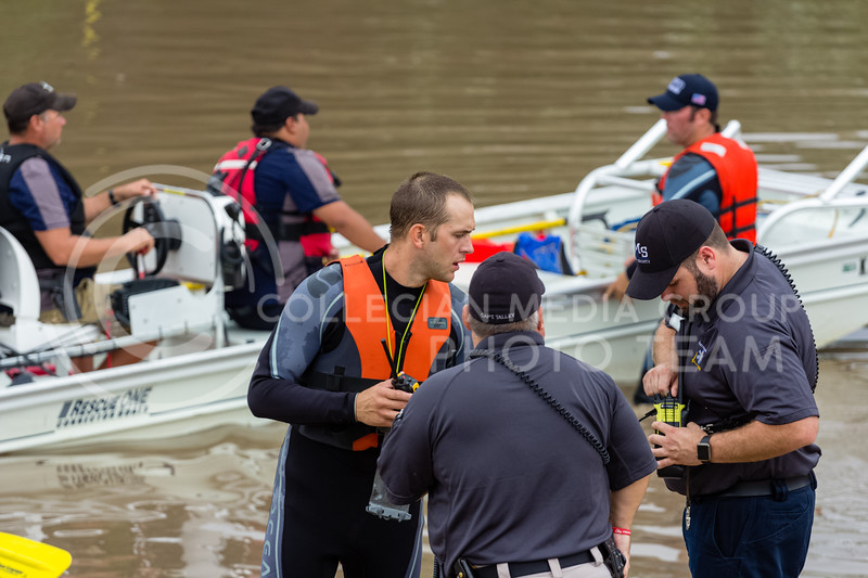 Three emergency responders tune their tactical radios to the same frequency while Manhattan Fire Department, Riley County Police Department and Pottawatomie County Sheriff's department work together to help recover Manhattan Ks residents trapped by flood waters on Monday Sept 3rd 2018 (Alex Shaw | Collegian Media Group)