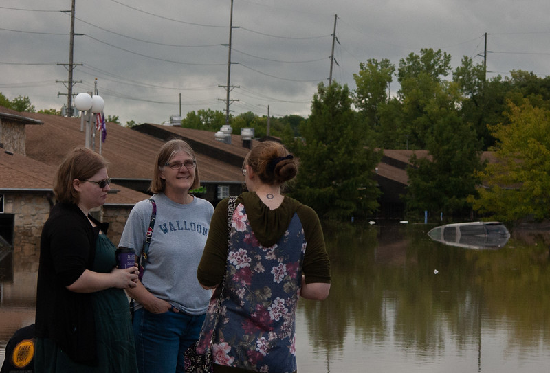 Talking to her daughter, Anne Higley co-owner of Goblin Games, mother Carrol Higley stands in front of the submerged store. Anne and Joseph Wyatt heard of the flooding earlier that morning and had just arrived to asses damages. (Rowan Jones | Collegian Media Group)