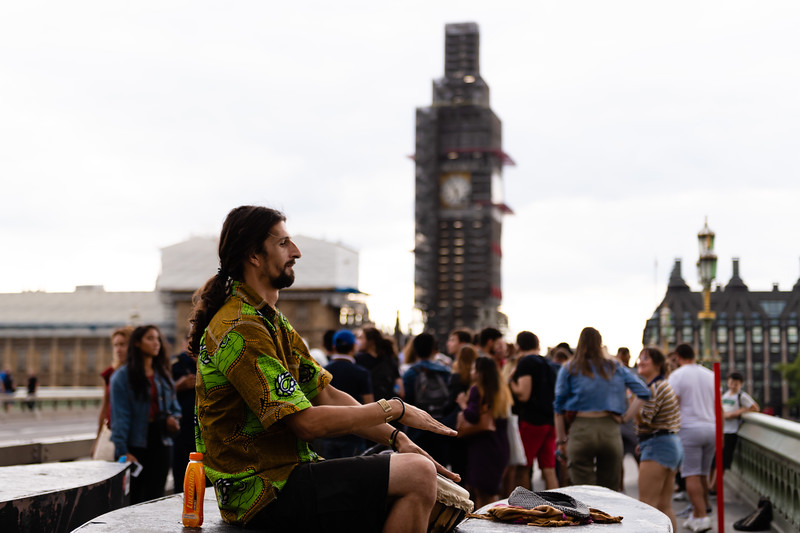 On Westminster Bridge a local percussionist plays a Djembe drum for pedestirans walking across the bridge. (Olivia Bergmeier | Collegian Media Group)