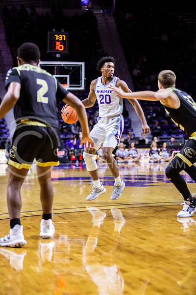 Senior forward Xavier Sneed scans the court for an open play during K-State's basketball team's home opener against ESU in Bramlage Coliseum on Oct. 25, 2019. The Wildcats held the Hornets 86-49. (Logan Wassall | Collegian Media Group)