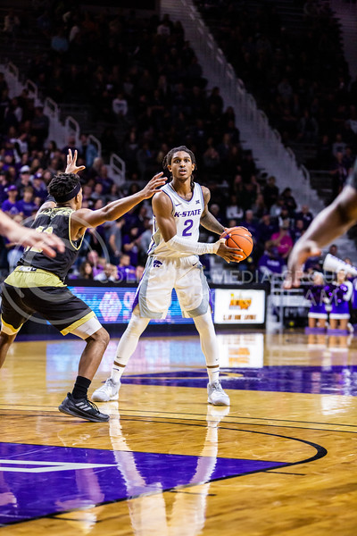 Junior guard Cartier Diarra scans the court for an open play during K-State's basketball team's home opener against ESU in Bramlage Coliseum on Oct. 25, 2019. The Wildcats held the Hornets 86-49. (Logan Wassall | Collegian Media Group)
