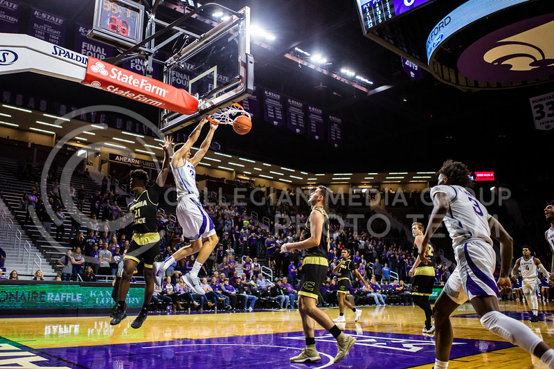 Senior forward Pierson McAtee leaps up for a dunk during K-State's basketball team's home opener against ESU in Bramlage Coliseum on Oct. 25, 2019. The Wildcats held the Hornets 86-49. (Logan Wassall | Collegian Media Group)
