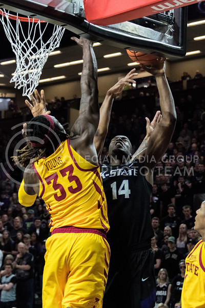 With his eyes closed, K-State foward Makol Mawien jumps up to get a rebound before the Iowa State defense can. Mawien had 8 rebounds during Saturday's game at Bramlage Coliseum. (Alex Todd | Collegian Media Group)