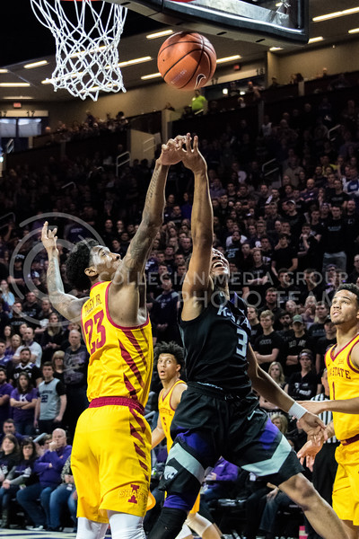 Jumping just in time, K-State guard Kamau Stokes manages to get a rebound before Iowa State's Zoran Talley Jr. can. (Alex Todd | Collegian Media Group)