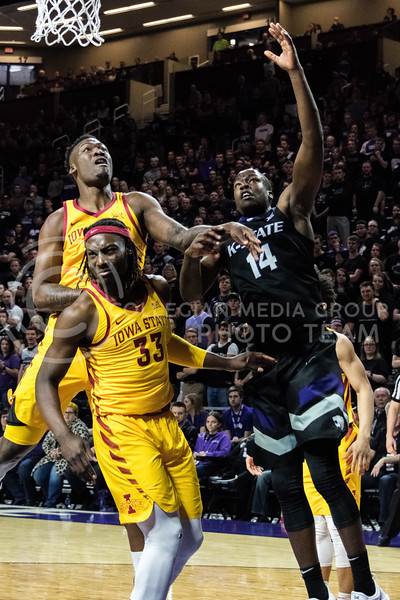 K-State foward Makol Mawien jumps up to get a rebound as he's fouled by Iowa State foward Solomon Young during Saturdays game. (Alex Todd | Collegian Media Group)