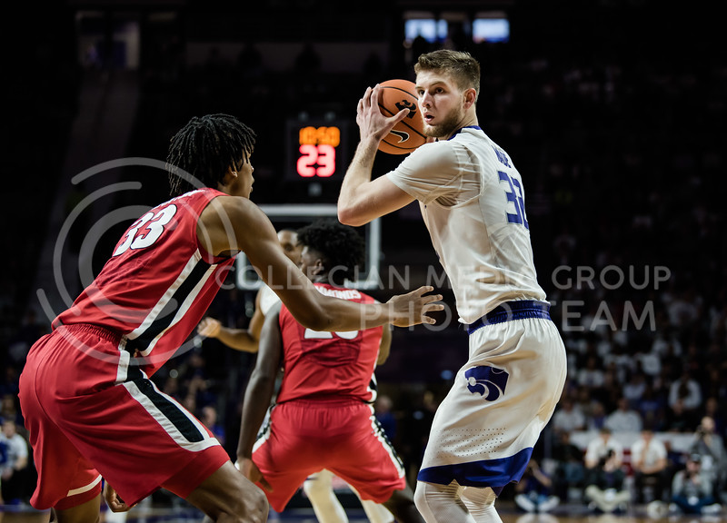 Looking for an opening for a pass to a fellow teammate, Kansas State Wildcat Dean Wade holds onto the ball tightly and away from the defending Georgia Bulldog Nicolas Claxton. On Saturday at the thunderous Bramlage Coliseum, KSU took another win over the UGA Bulldogs with a final score of 56-51.<br /> (Olivia Bergmeier   Collegian Media Group)