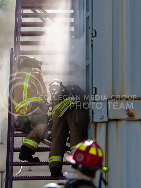 Manhattan Fire Department members check the amount of smoke billowing out of the practice building. On Tuesday, June 26, 2018, the fire department ran controll burns for the recruits. (Olivia Bergmeier | Collegian Media Group)