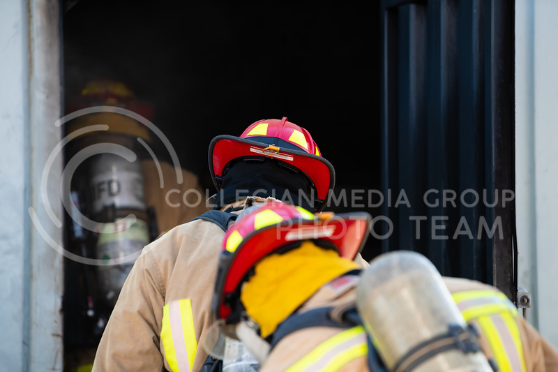 Recruits step into the practice building while other Manhattan Fire Department members light a fire at the other end of the building. On Tuesday, June 26, 2018, the fire department ran controll burns for the recruits. (Olivia Bergmeier | Collegian Media Group)