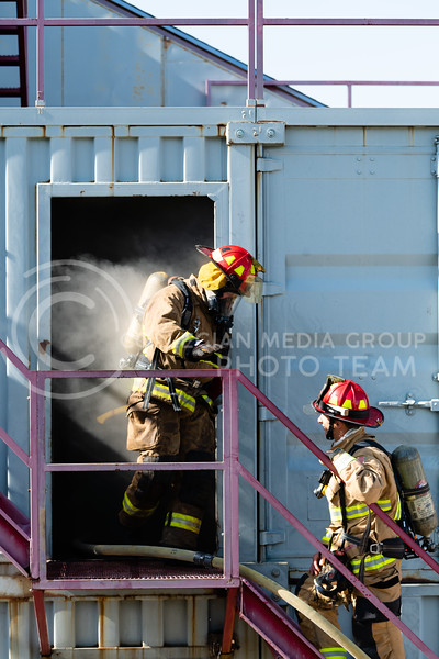 Recruit Millican walks from the burning traning building after subduing the fire within. On Tuesday, June 26, 2018, the fire department ran controll burns for the recruits. (Olivia Bergmeier | Collegian Media Group)
