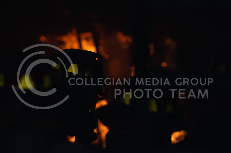 A Manhattan Fire Department firefighter tells recruits what the expect as the control burn flames at the opposite end of the building. On Tuesday, June 26, 2018, the fire department ran controll burns for the recruits. (Olivia Bergmeier | Collegian Media Group)