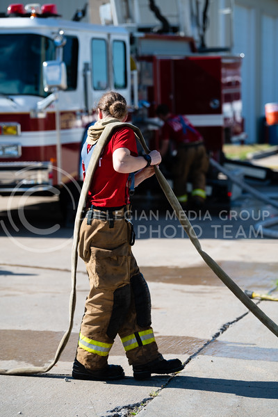 A Manhattan Fire Department recruit helps to drain the water from a fire hose after a drill ran in the controll fire practice building. On Tuesday, June 26, 2018, the fire department ran controll burns for the recruits. (Olivia Bergmeier | Collegian Media Group)