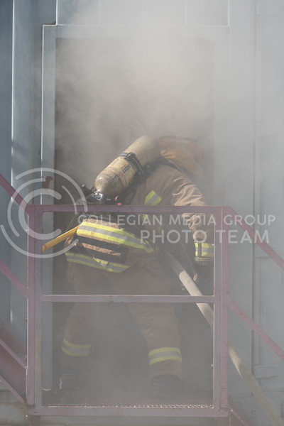 Dragging the fire hose within the building, a Manhattan Fire Department recruit advances into the building after a fire located at the other end. On Tuesday, June 26, 2018, the fire department ran controll burns for the recruits. (Olivia Bergmeier | Collegian Media Group)