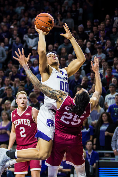 Sophomore guard Mike McGuirl is fouled as he leaps up for a shot during K-State's basketball game against Denver in Bramlage Coliseum on Nov. 12, 2018. The Wildcats defeated the Pioneers 64-56. (Logan Wassall | Collegian Media Group)