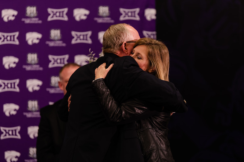 K-State athletic director Gene Taylor welcomes Mrs. Klieman to the K-State family through a bouquet and an embrace at a press conference on Wednesday. New head coach Chris Klieman was welcomed to Manhattan on Dec. 12, 2018, to head into the next football season. (Olivia Bergmeier | Collegian Media Group)