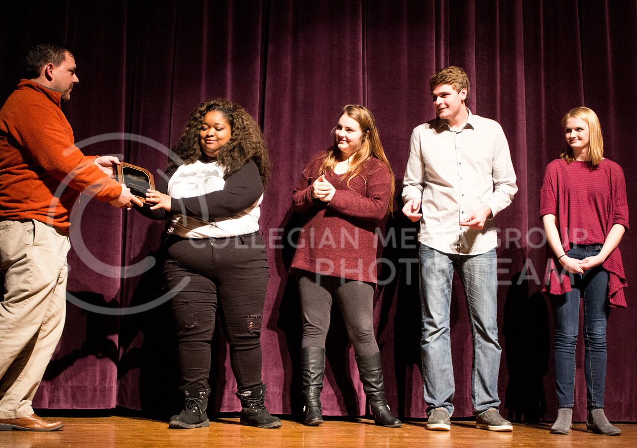 The improv group Black and White and Red All Over recieve an award from thier advisor after winning the College Improve Heartland Regional. Team members include Casha Mills, senior in English, Nate Kochuyt, freshman in theater, Brigid Reilly, senior in theater, and Emma Pirotte, freshman in secondary education. (Regan Tokos | The Collegian)