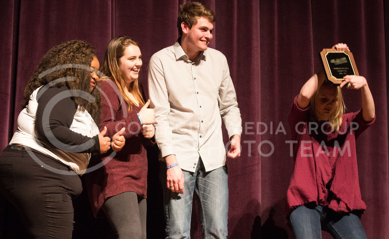 The improv group Black and White and Red All Over recieve an award from thier team after winning the College Improve Heartland Regional. Team members include Casha Mills, senior in English, Nate Kochuyt, freshman in theater, Brigid Reilly, senior in theater, and Emma Pirotte, freshman in secondary education. (Regan Tokos | The Collegian)