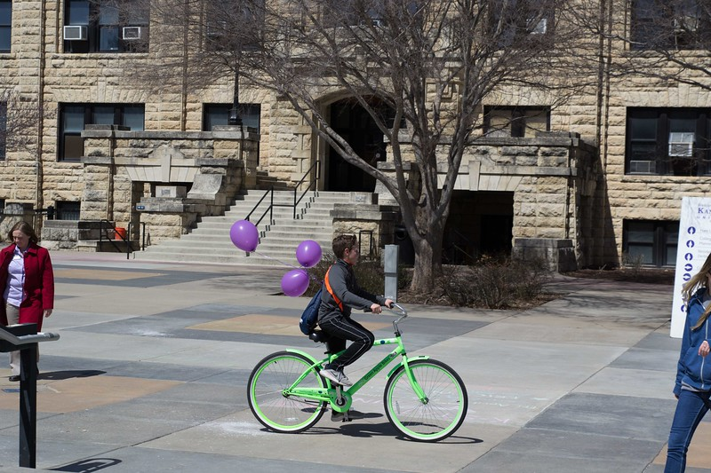 Nothing like purple balloons to show K-State pride as a bicyclist rides around the Union Courtyard at Open House on Saturday, April 7. K-State's Open House was filled with fun activities, food, and plenty of opportunities to explore the vast options K-State has to offer. (Hannah Greer | Collegian Media)