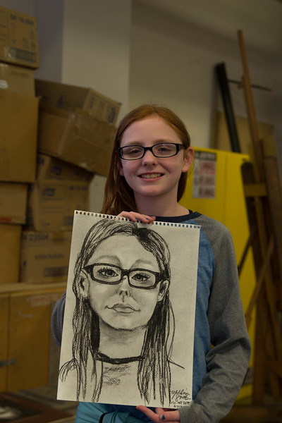 While visiting K-State's Open House on Saturday this young girl got her portrait drawn by one of the University's art students. K-State's Open House was filled with fun activities, food, and plenty of opportunities to explore the vast options K-State has to offer.   (Hannah Greer | Collegian Media)